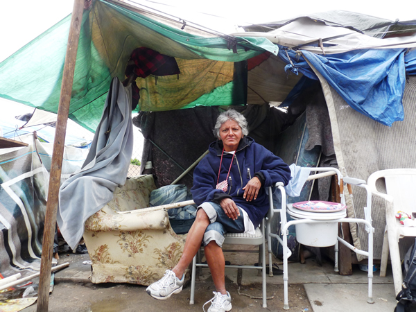 Cynthia proudly sits outside the makeshift home she has constructed on the sidewalk in Fresno, California, a US city with over 3,000 homeless people and less than 300 shelter beds. Photo by Christopher Herring.