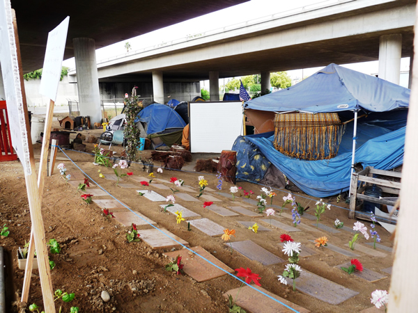 A makeshift encampment of a group of homeless people in Fresno, California, USA. The residents bordered their encampment with a homeless memorial with cardboard gravestones with the names of those who passed away on the streets marked by artificial flowers – an expression of both the dignity and resilience of this community and sad reminder of the perils faced by those without shelter. Photo by Christopher Herring.