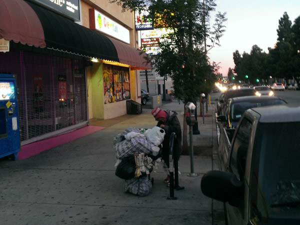 Woman with cart: A homeless woman in Los Angeles, U.S.A. arranges her meager belongings before looking for a place to sleep for the night.  Photograph by Benjamin Clavan, 2015.
