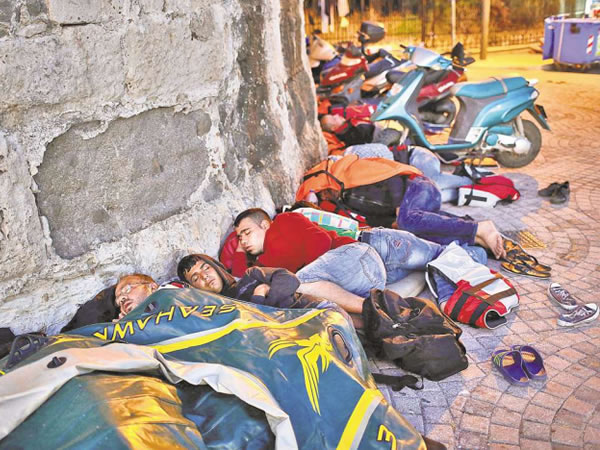 FLEEING EN MASSE: Migrants from Syria sleep along the walls of a 14th-century fortress in Kos, Greece. (WIN MCNAMEE/GETTY IMAGES/WALL STREET JOURNAL AUG. 2015 FRONT PAGE).